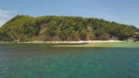 Vista aérea de la isla tropical verde con las montañas, playa de la arena y chozas de la pesca almacen de video
