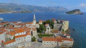 Vista aérea de la isla vieja de la playa y de San Nicolás de la ciudad de Budva, Montenegro 1 metrajes