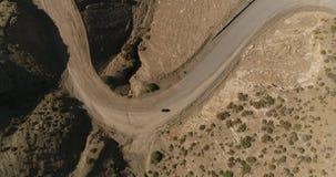 Vista aérea de la motocicleta vieja que conduce en la carretera nacional en montaña Vuelo cinem?tico del tiro del abej?n sobre el almacen de metraje de vídeo