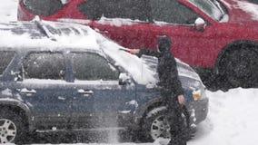 Vista aérea de la nieve y del hielo de la limpieza del hombre de su ventana del escudo de viento del coche almacen de video