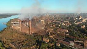 Vista aérea de la planta industrial con los tubos que fuman cerca de la ciudad Zona industrial almacen de video