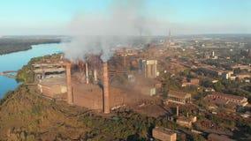 Vista aérea de la planta industrial con los tubos que fuman cerca de la ciudad Zona industrial almacen de metraje de vídeo