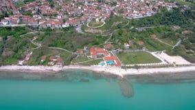 Vista aérea de la playa imponente debajo de un pueblo turístico, Athitos Halkidiki Grecia, movimiento circular de la turquesa por almacen de video