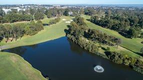 Vista aérea de la presa del campo de golf con la fuente rodeada por los espacios abiertos, los árboles y las arcones Fotos de archivo