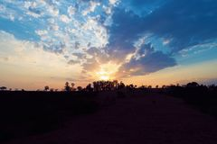 Vista aérea de la puesta del sol de un campo con los rayos de sol del bosque fotos de archivo libres de regalías