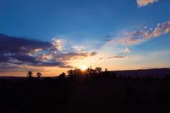 Vista aérea de la puesta del sol de un campo con los rayos de sol del bosque imágenes de archivo libres de regalías