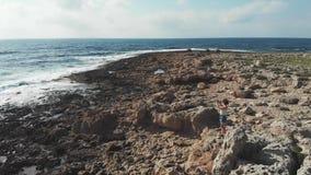Vista aérea de la situación femenina de la mujer en las rocas que toman imágenes del mar ondulado Ondas fuertes que golpean la co
