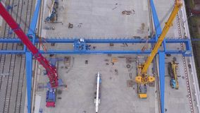 Vista aérea de las grúas de construcción rojas y amarillas instaladas cerca de los contenedores para mercancías amarillos y del f almacen de metraje de vídeo