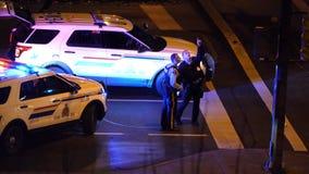 Vista aérea de las luces de emergencia rojas y azules de la discusión de los coches policía y de los hombres de la policía del ac metrajes