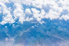 Vista aérea de las nubes blancas, del cielo azul y de la tierra Imágenes de archivo libres de regalías