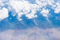 Vista aérea de las nubes blancas, del cielo azul y de la tierra Imagen de archivo libre de regalías