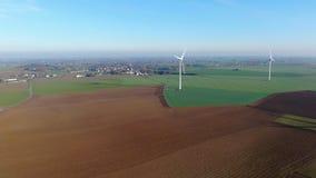 Vista aérea de las turbinas de viento y de los campos agrícolas en un día de invierno azul hermoso metrajes