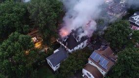 Vista aérea de los coches de bomberos y del aparato que luchan un fuego de la casa almacen de metraje de vídeo