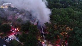 Vista aérea de los coches de bomberos y del aparato que luchan un fuego de la casa metrajes