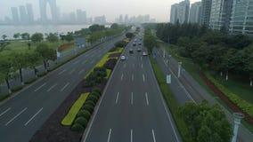 Vista aérea de los coches que corren en el camino de ciudad en la puesta del sol, China almacen de video