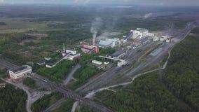 Vista aérea de los edificios industriales de la planta con las chimeneas altas rodeadas por el sistema de producción del bosque almacen de metraje de vídeo