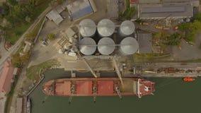 Vista aérea de los elevadores de grano grandes en el mar Cargamento del grano en una nave Acceso Buque de carga almacen de metraje de vídeo