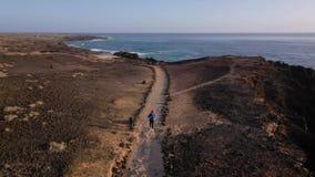 Vista aérea de los funcionamientos de la mujer a lo largo de la reserva de naturaleza de la costa en la salida del sol Forma de v almacen de video