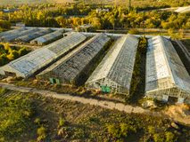 Vista aérea de los invernaderos agrícolas de cristal exteriores el día de verano f imagenes de archivo