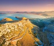 Vista aérea de montañas, camino, árboles, mar azul en la puesta del sol Foto de archivo libre de regalías