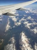 A vista aérea de montanhas rochosas e o avião voam Imagens de Stock