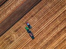 Vista aérea de 2 tratores que trabalham no campo da colheita imagem de stock