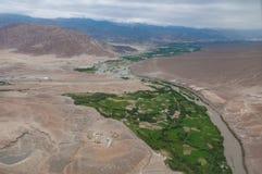 Vista aérea de uma angra pequena da vila e do rio em um vale verde cercado por montanhas rochosas do deserto Fotografia de Stock