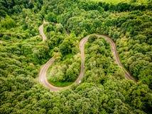Vista aérea de uma estrada de enrolamento extrema acima nas montanhas Imagem de Stock