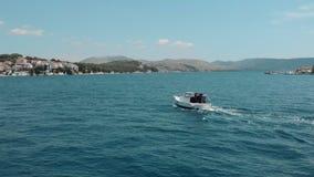 A vista aérea de uma lancha velha pequena com um homem move-se no mar claro azul video estoque
