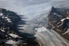 Vista aérea de uma parte dianteira e de montanhas da geleira em Gronelândia Imagens de Stock