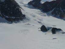 Vista aérea de un afloramiento rocoso que muestra a través de un glaciar Imagen de archivo libre de regalías