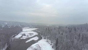 Vista aérea de un bosque nevoso, de un pequeño río y de una ciudad en las montañas de Tatra, Polonia Fotos de archivo
