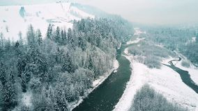 Vista aérea de un bosque, de un pequeño río y de remontes alpinos distantes en la nieve Las montañas de Tatra, Polonia Fotos de archivo libres de regalías