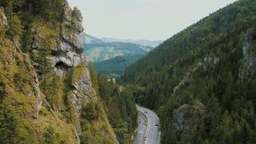 Vista aérea de un camino de la montaña en una garganta profunda hermosa Los coches se mueven en un camino de la montaña metrajes