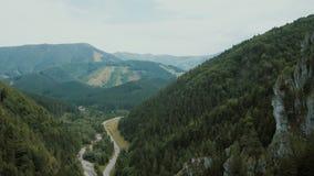 Vista aérea de un camino de la montaña en una garganta profunda hermosa Los coches se mueven en un camino de la montaña almacen de metraje de vídeo