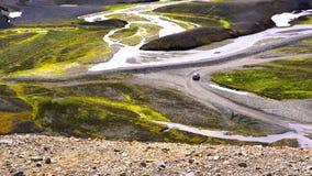 Vista aérea de un coche que corre en la montaña hermosa y la corriente en Lanmannalaugar almacen de video