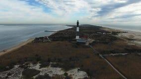 Vista aérea de un faro y de un cierre de la línea de la playa para arriba en Sunny Winter Day como visto por un abejón metrajes