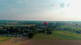 Vista aérea de un globo del aire caliente que flota a lo largo del campo de Amish almacen de metraje de vídeo