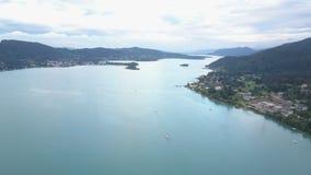 Vista aérea de un lago grande en montañas Movimientos del barco en el lago Klagenfurt Carinthia Austria metrajes