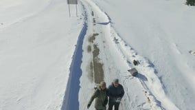 Vista aérea de un par que se coloca en el camino nevoso del invierno metrajes