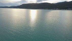Vista aérea de un pequeño yate en un lago grande en montañas Movimientos del barco en el lago Klagenfurt Carinthia Austria almacen de video