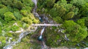 Vista aérea de un puente peatonal a través de una garganta con una cascada, visión superior Imagen de archivo libre de regalías