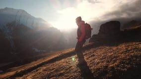 Vista aérea de un tiro épico de una muchacha que camina al borde de una montaña como silueta en una puesta del sol hermosa metrajes