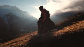 Vista aérea de un tiro épico de una muchacha que camina al borde de una montaña como silueta en una puesta del sol hermosa almacen de video