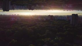 Vista aérea de una ciudad con muchos árboles verdes en el fondo del cielo de la salida del sol, efecto del espejo del horizonte P ilustración del vector
