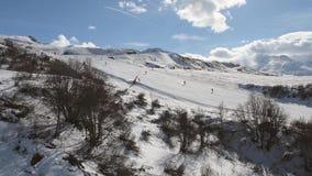 Vista aérea de una cuesta alpina del esquí mientras que viaja cuesta arriba metrajes