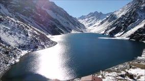 Vista aérea de una nieve de la laguna y de la montaña almacen de video
