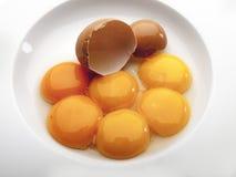 Vista aérea de una placa blanca con seis huevos y una cáscara 3 fotos de archivo
