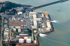 Vista aérea de una planta industrial que utiliza el agua de mar y devoluciones él detrás Uso de recursos naturales, contaminación fotografía de archivo libre de regalías