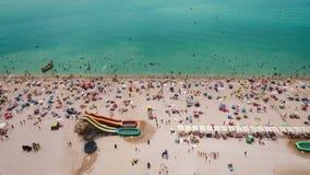 Vista aérea de una playa apretada en un día caliente soleado Arena y paraguas amarillos almacen de video